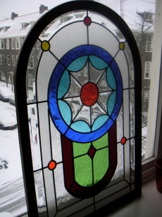 View on the snow through stained glass window, Amsterdam, Netherlands